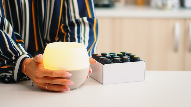 Zamknięcie dyfuzora olejków eterycznych po dodaniu do niego zapachu. aroma esencja zdrowotna, welness aromaterapia domowe spa zapach spokojna terapia, para terapeutyczna, leczenie zdrowia psychicznego;