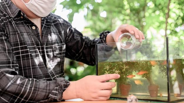 Zamknięcie i samodzielna kwarantanna w domu. karmienie ryb w ogrodzie. odłącz się od społeczności i zostań w domu. bądź bezpieczny. zdrowie psychiczne i dobre samopoczucie. nowa normalność i życie po covid-19.