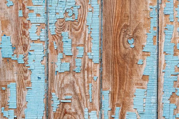 Zamknięcie na niebieskie drewniane panele ogrodzenia z bliska. łuszczenie starej farby na drewnianym płocie.