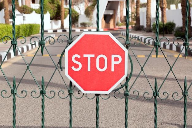 Zamknięta brama z czerwonym znakiem stopu przy wejściu do hotelu