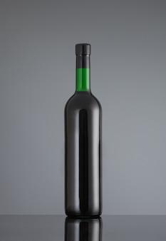 Zamknięta butelka czerwonego wina na szarym tle z odbiciem