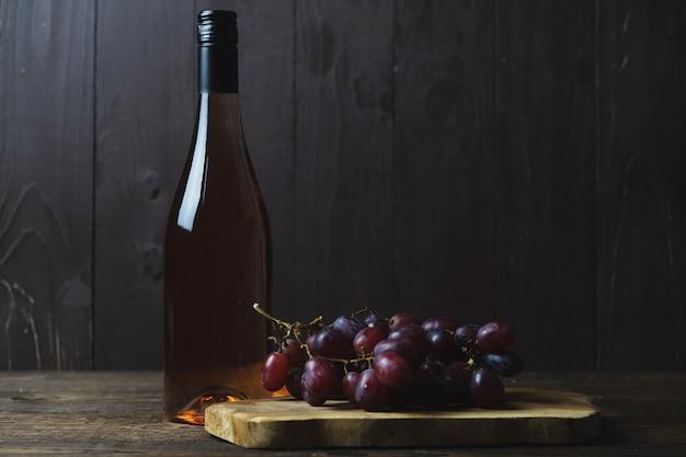 Zamknięta butelka wina różanego i kiść czerwonych beznasiennych winogron w pobliżu drewna