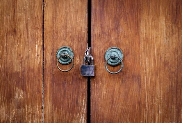 Zamknięta kłódka z łańcuchem przy brown drewnianym drzwiowym tłem