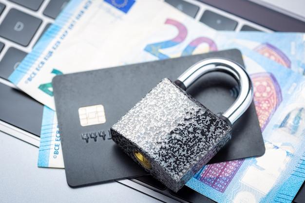 Zamknięta kłódka z pieniędzmi i kartą kredytową na klawiaturze laptopa