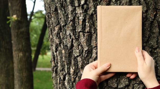 Zamknięta księga w okładce wykonanej z papieru rzemieślniczego w kobiecych rękach na tle kory drzewa w parku. skopiuj miejsce. pojęcie czytania, rekreacji i wypoczynku, nauki i edukacji.