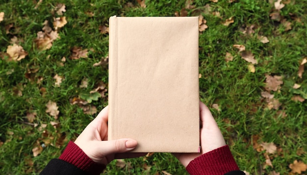 Zamknięta księga w okładce z papieru rzemieślniczego w kobiecych rękach z zieloną trawą i opadłymi żółtymi liśćmi w tle. płaski świeckich, widok z góry. szablon, układ. skopiuj miejsce.