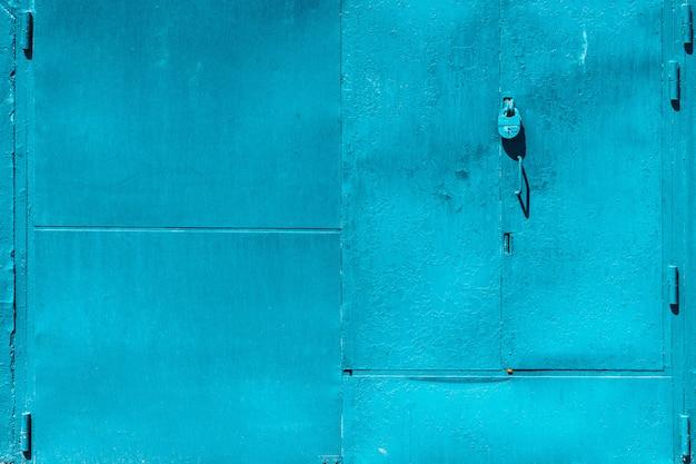 Zamknięta niedoskonała niebieska brama garażowa z kłódką z bliska. tekstura zamkniętego żelaznego drzwi z cyan obieranie farbą. łuszczące się plamy barwnika na nieczysty metalowej powierzchni. teksturowane tło szorstkich wyblakłych bram stalowych.