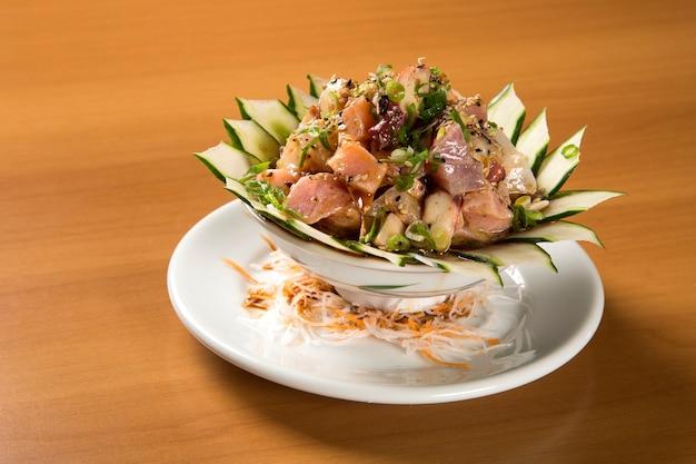 """Zamknięte danie japońskie: duża miska ryżu zmieszana ze świeżą rybą (łososiem i innymi rybami) na wierzchu o nazwie """"chirashi""""."""