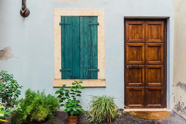 Zamknięte drewniane drzwi i okna w tradycyjnym stylu na elewacji domu.