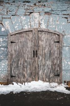 Zamknięte drewniane drzwi ze śniegiem z przodu