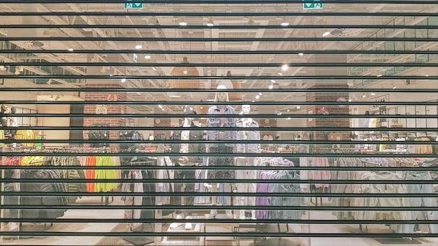 Zamknięte drzwi do sklepu z modą podczas pandemii covid 19. fotografia mobilna. zamknięcie centrum handlowego objętego kwarantanną i zatrzymanie sprzedaży detalicznej. figurka i manekin za kratkami, siatka, roleta.