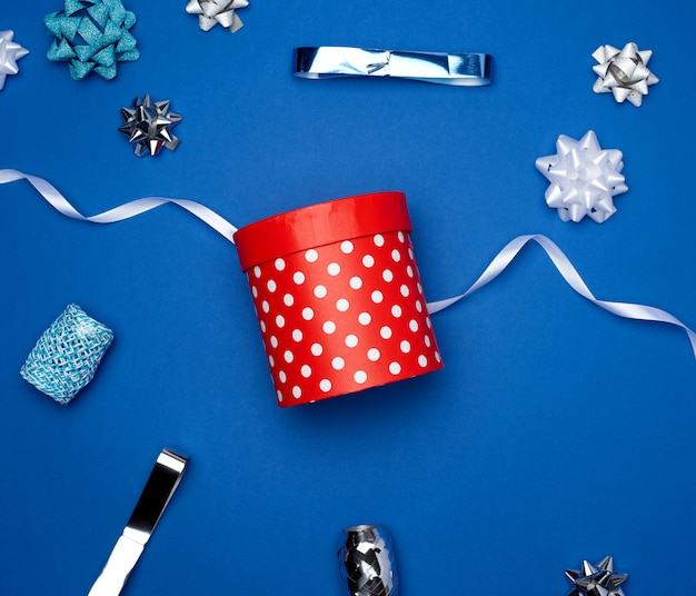 Zamknięte kartonowe czerwone pudełko z białymi kropkami i czerwoną jedwabną wstążką na niebieskim tle