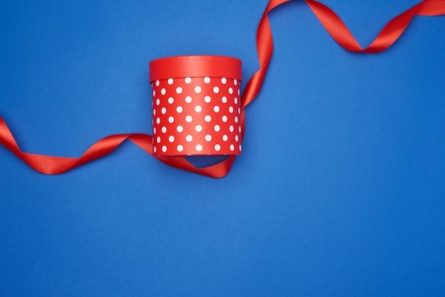 Zamknięte kartonowe czerwone pudełko z białymi kropkami i czerwoną jedwabną wstążką