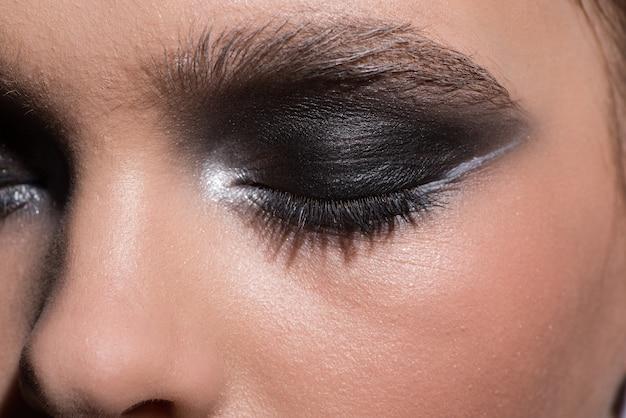 Zamknięte kobiece oko z nowoczesnym modnym makijażem. zbliżenie
