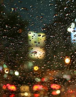 Zamknięte krople deszczu na przedniej szybie samochodu podczas jazdy po miejskiej ulicy w nocy