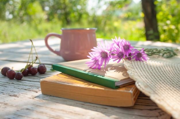 Zamknięte książki, różowe kwiaty, wiśniowe jagody i różowy kubek na drewnianym stole w ogrodzie