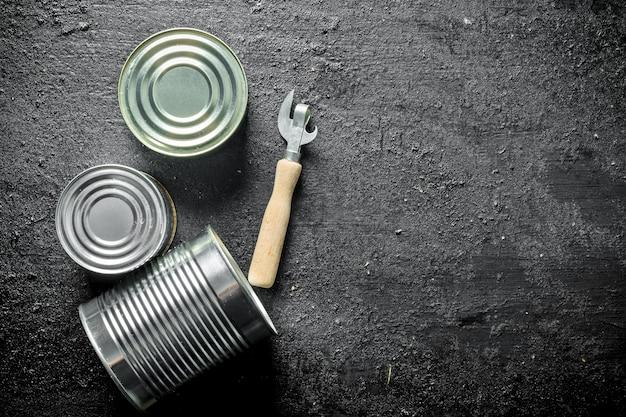 Zamknięte metalowe puszki z konserwami na czarnym rustykalnym stole