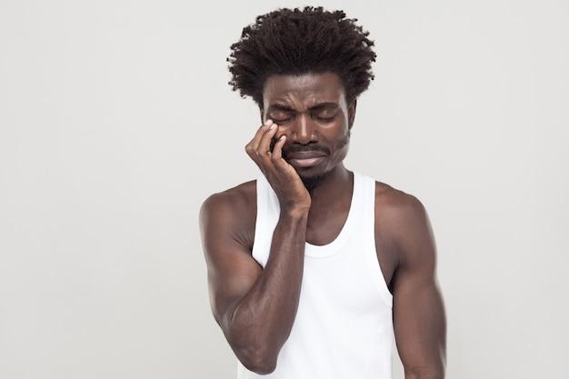 Zamknięte oczy i płacz. nieszczęśliwy afro mężczyzna z wąsami souvarova, płacze i ma depresję. strzał w pomieszczeniu