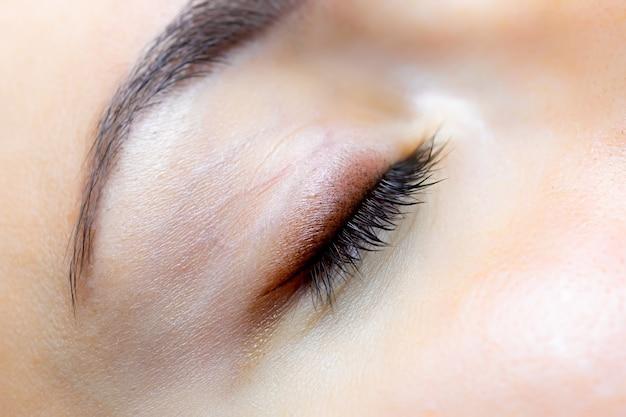Zamknięte oko i zakończona praca makijażu permanentnego powiek i rzęs