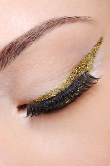Zamknięte oko kobiecego oka z jasną błyszczącą złotą strzałką eyeliner