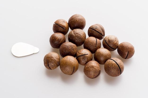 Zamknięte orzechy makadamia na białym tle z kluczem do otwierania - zdjęcie