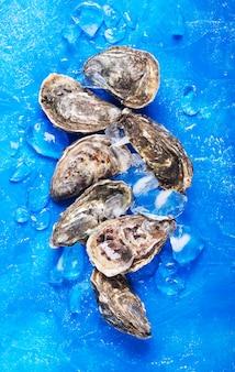 Zamknięte ostrygi na błękitnym tle. zdrowe owoce morza, orientacja pionowa