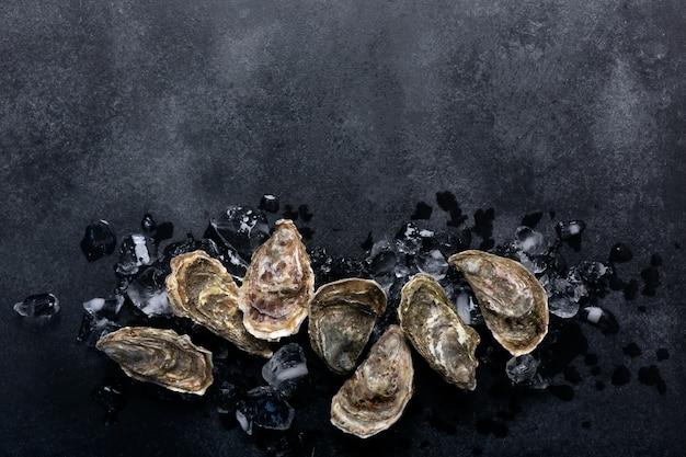 Zamknięte ostrygi na czarnym chalkboard tle. zdrowe owoce morza