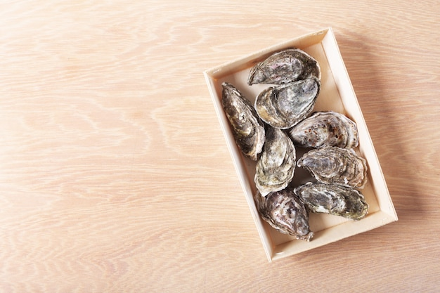 Zamknięte ostrygi na drewnianym tle. zdrowe owoce morza. skopiuj miejsce, widok z góry