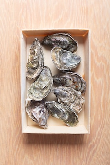 Zamknięte ostrygi w pudełku na drewnianym tle. zdrowe owoce morza