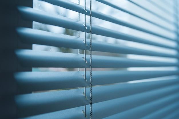 Zamknięte plastikowe żaluzje w oknie z odbiciem