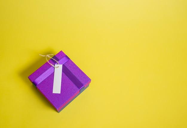 Zamknięte pudełko z pustą metką na żółtym polu. fioletowe pudełko upominkowe. sprzedaż ogłoszeń