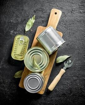 Zamknięte puszki z jedzeniem na drewnianej desce do krojenia z otwieraczem i liściem laurowym na czarnym rustykalnym stole