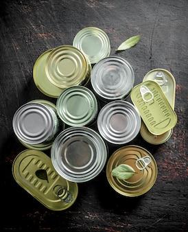 Zamknięte puszki z konserwami na ciemnym rustykalnym stole