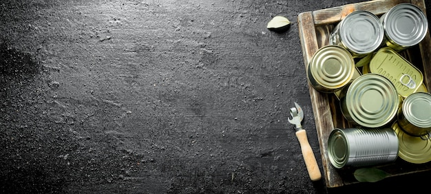 Zamknięte puszki z konserwami na drewnianej tacy. na czarnej powierzchni rustykalnej