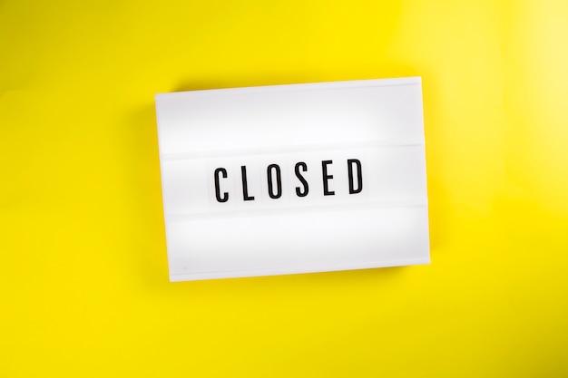 Zamknięte słowo na vintage billboard lightbox na żółtym tle na białym tle