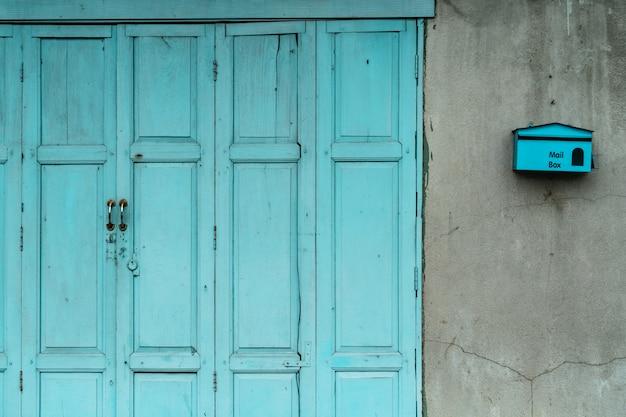 Zamknięte zielone lub niebieskie drewniane drzwi i pusta skrzynka na pękniętej betonowej ścianie domu. stary dom z krakingową cementową ścianą.