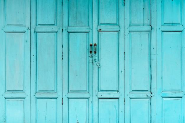 Zamknięte zielone lub niebieskie drewniane drzwi. rocznika dzwi wejściowy abstrakta tło. opuszczony stary dom.