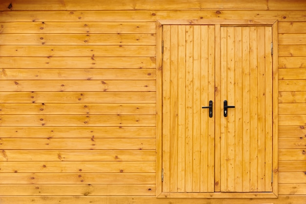 Zamknięte żółte drewniane drzwi na stodole. drzwi z desek. ściana z desek. tekstura tło stodoły wsi.