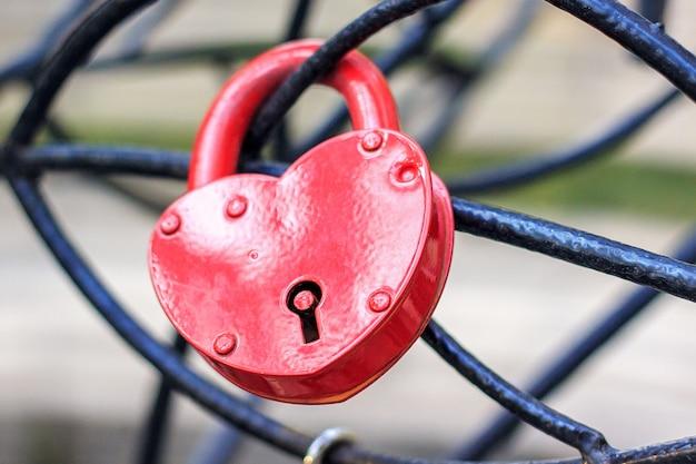 Zamknięty czerwony zamek w kształcie serca wisi na żelaznej konstrukcji.
