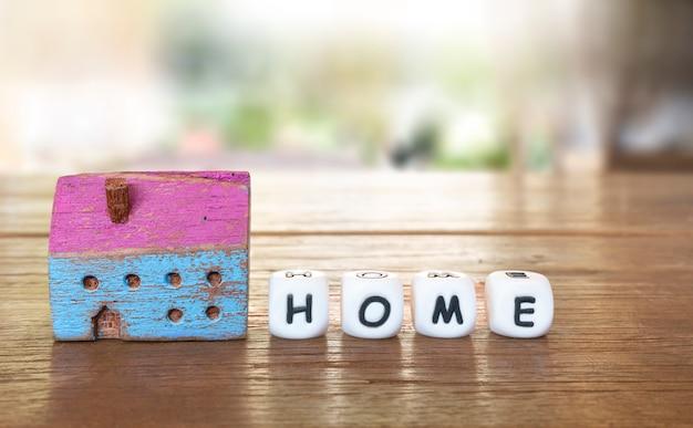 Zamknięty kolorowy mały malowany drewniany model domu z małymi kostkami alfabetu pisowni domu.