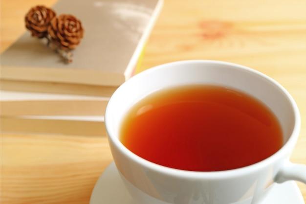 Zamknięty kubek gorącej herbaty na drewnianym stole z niewyraźne stos książek i suche szyszki