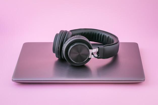 Zamknięty laptop i słuchawki. metaliczny notatnik i czarne przenośne słuchawki