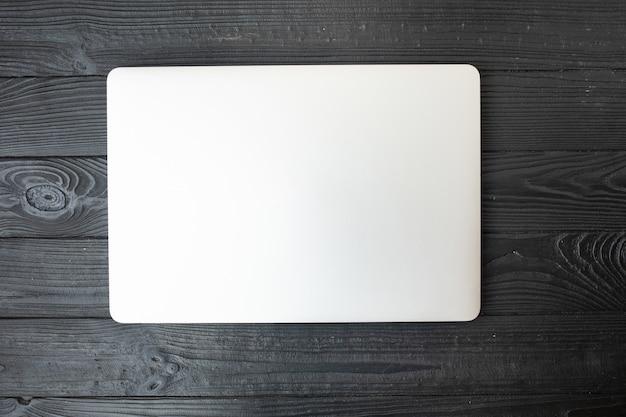 Zamknięty Laptop Na Drewnianym Tle Premium Zdjęcia