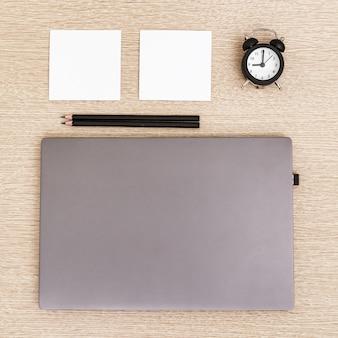 Zamknięty laptop na lekkim drewnianym stole z budzikiem, notatkami i czarnymi ołówkami