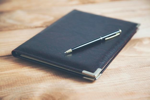Zamknięty notatnik i długopis na drewnianym stole