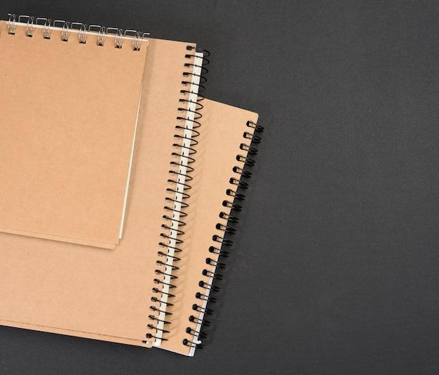 Zamknięty notatnik z brązowymi arkuszami na czarnym tle, z bliska
