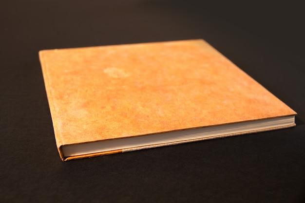 Zamknięty pusty notatnik odizolowywający na czerni