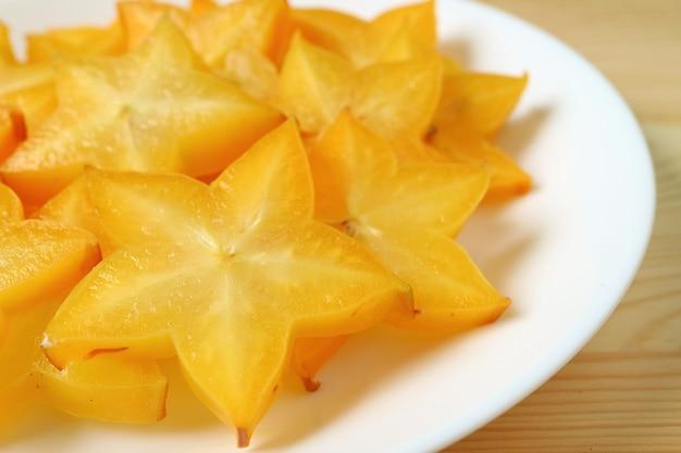 Zamknięty wibrujący kolor świeże star fruit plastry w wielu kawałkach serwowane na białym talerzu