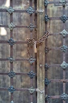 Zamknięty zamek z łańcuchem na starych stalowych drzwiach, zamki na zardzewiałych metalowych drzwiach