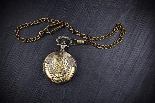 Zamknięty zegarek kieszonkowy z brązu z herbem związku radzieckiego i łańcuszkiem na ciemnej powierzchni.